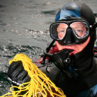 Photograph of scuba-diver with a net of shellls